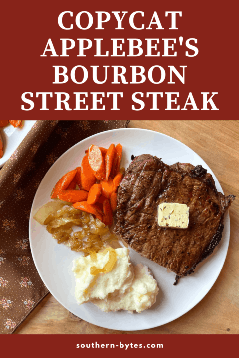 A pin image of a cooked bourbon street steak on a dish with cooked carrots, onions, mashed potatoes, and fried onions.