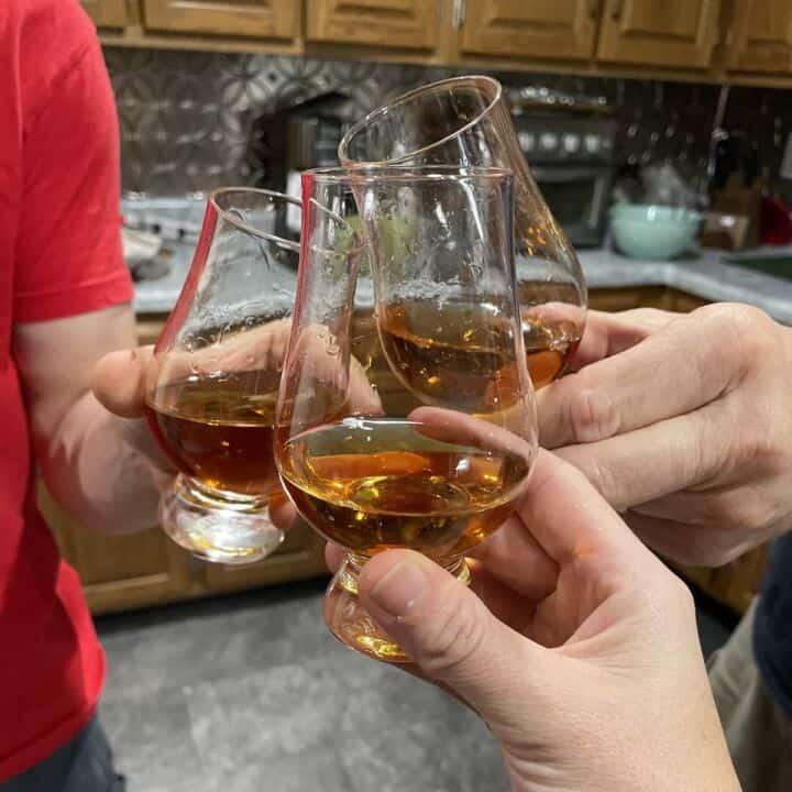 three glasses of bourbon toasting