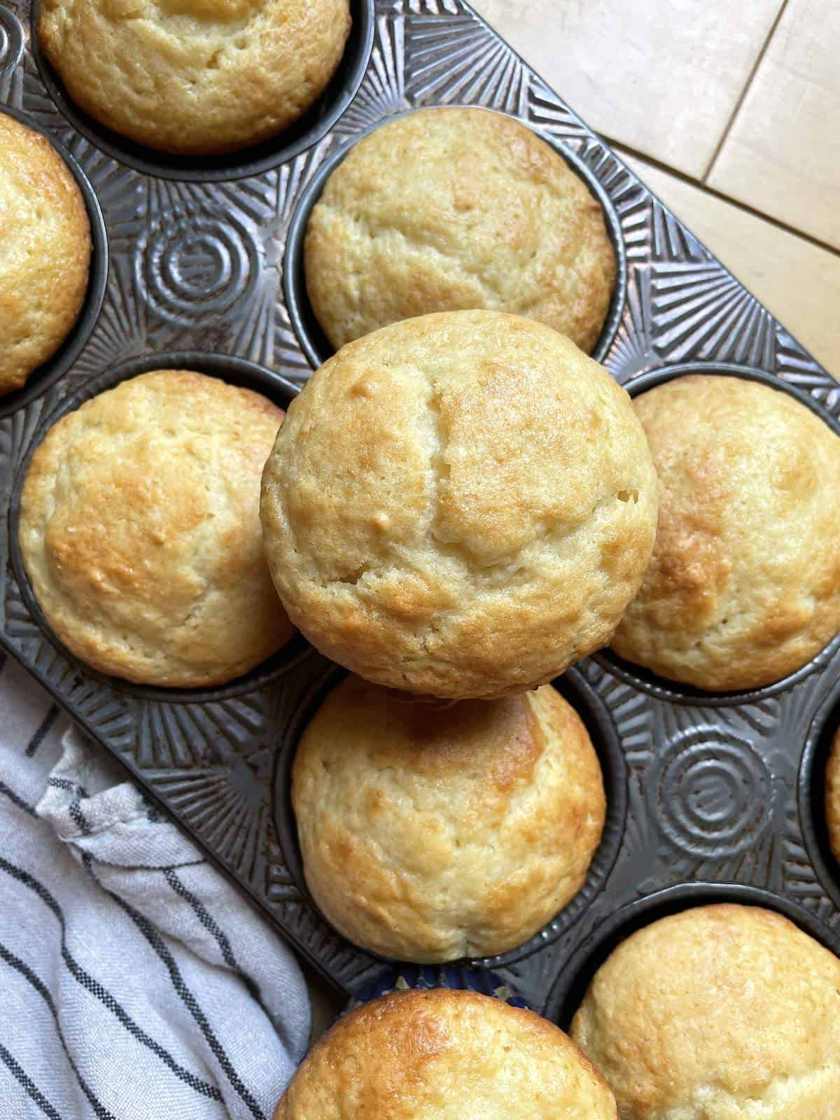 A pan of buttermilk muffins with one on top.