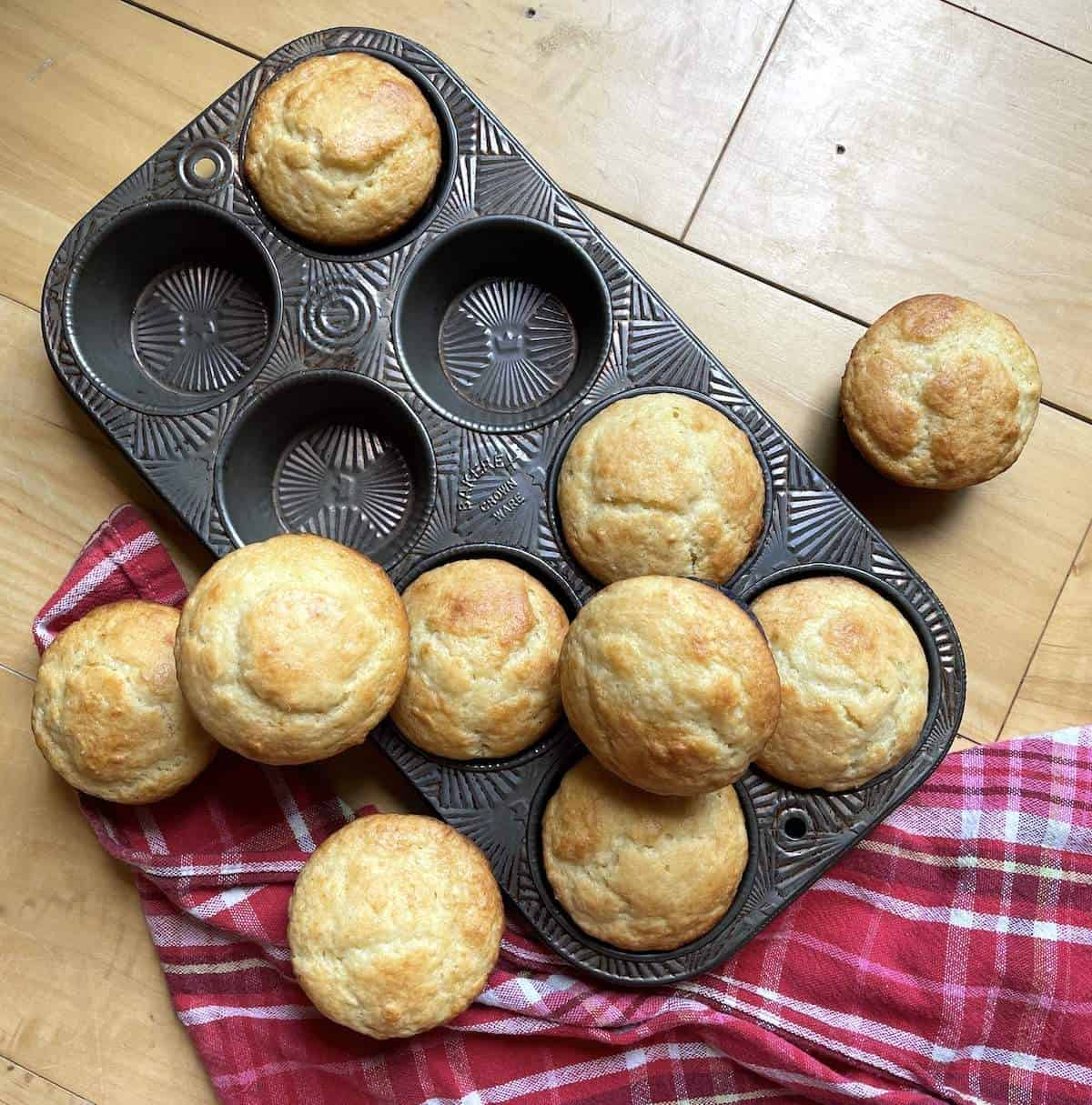 A pile of buttermilk muffins on a muffin tin with a plaid napkin.