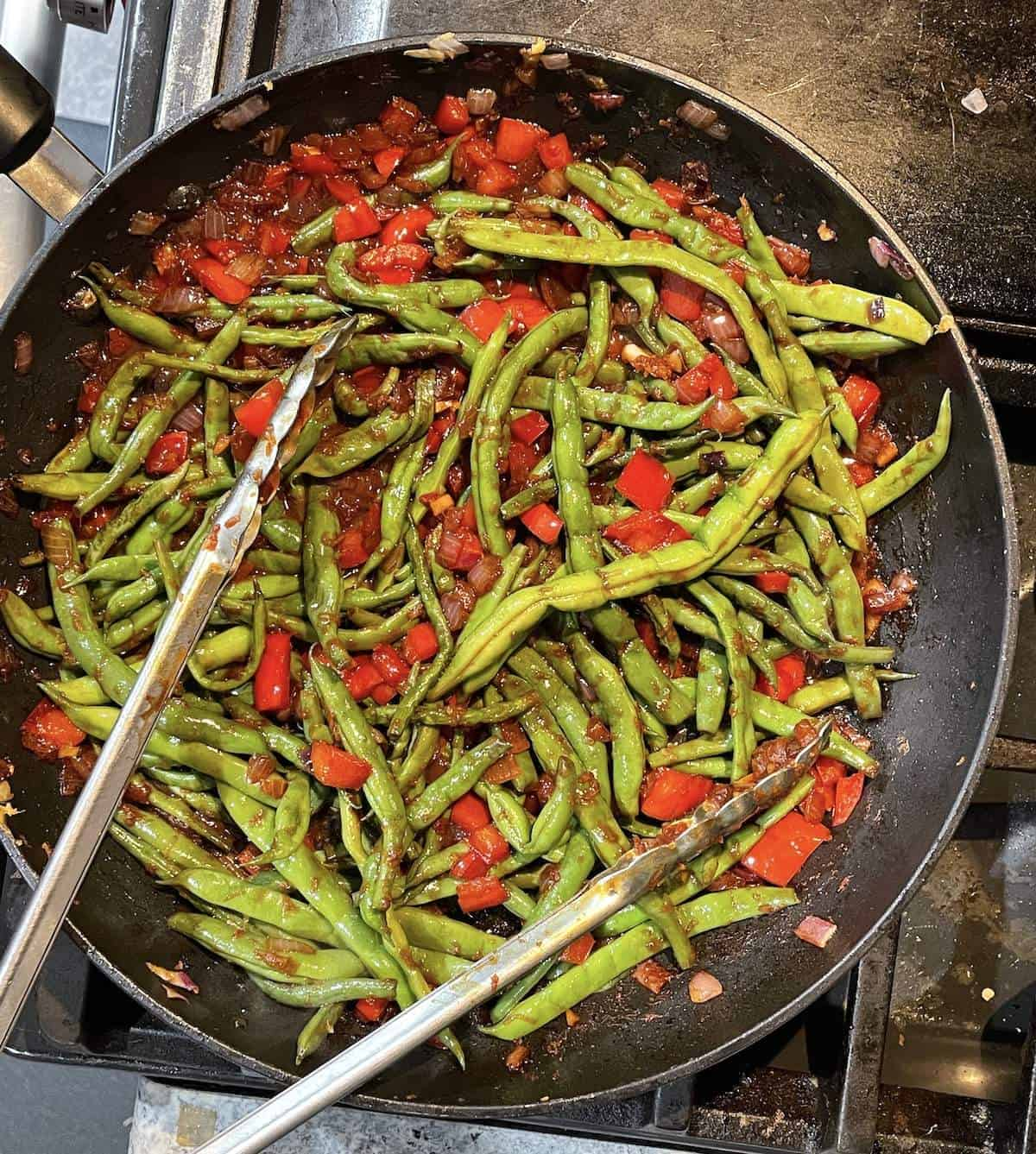 Green beans, red onion, and red bell pepper cooking in a frying pan.