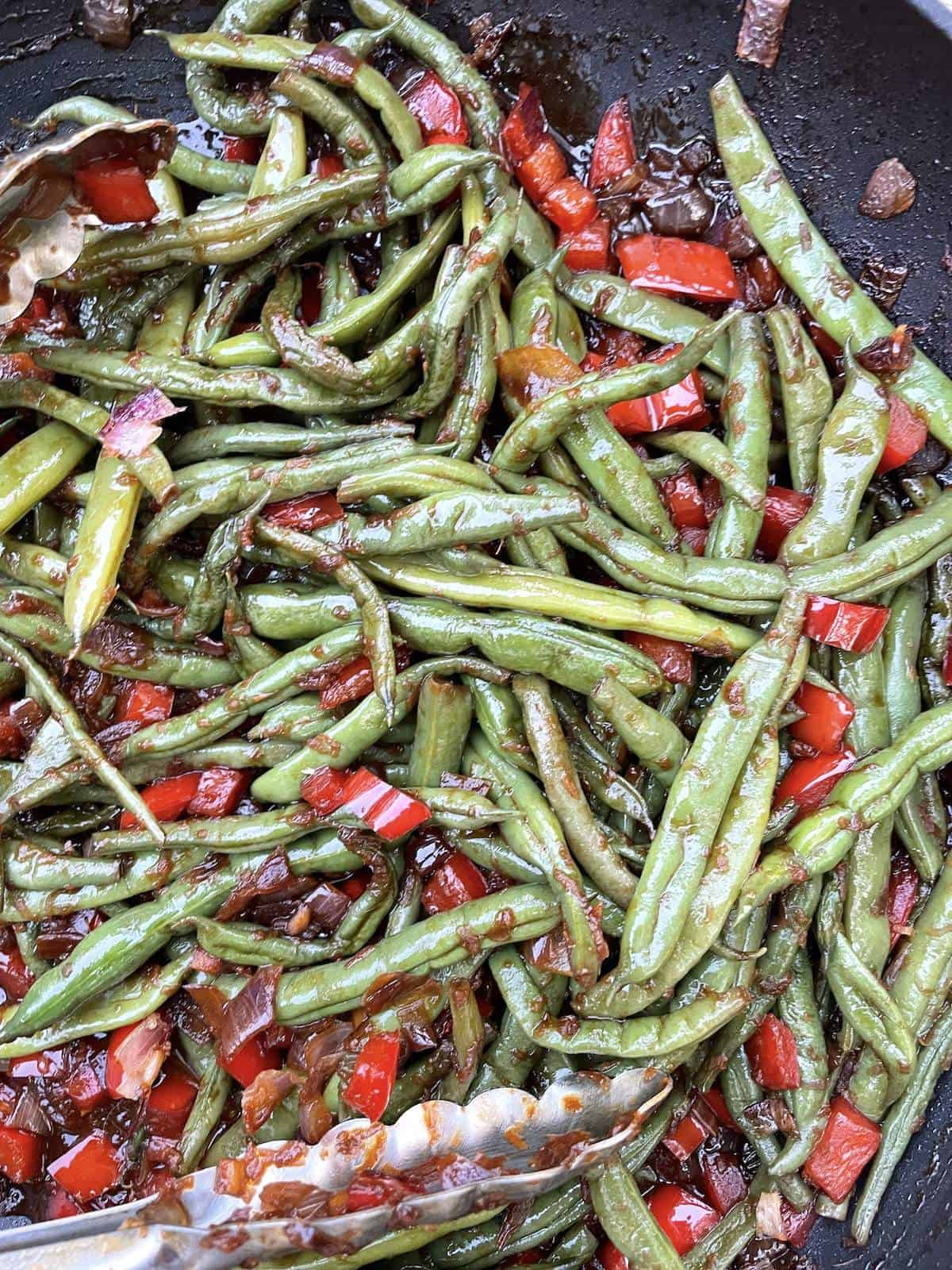 A frying pan filled with sautéed Peruvian green beans and a pair of tongs.