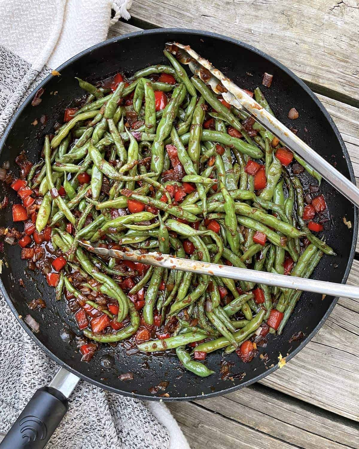 A frying pan of Peruvian green beans with bell pepper and onions and a pair of tongs.