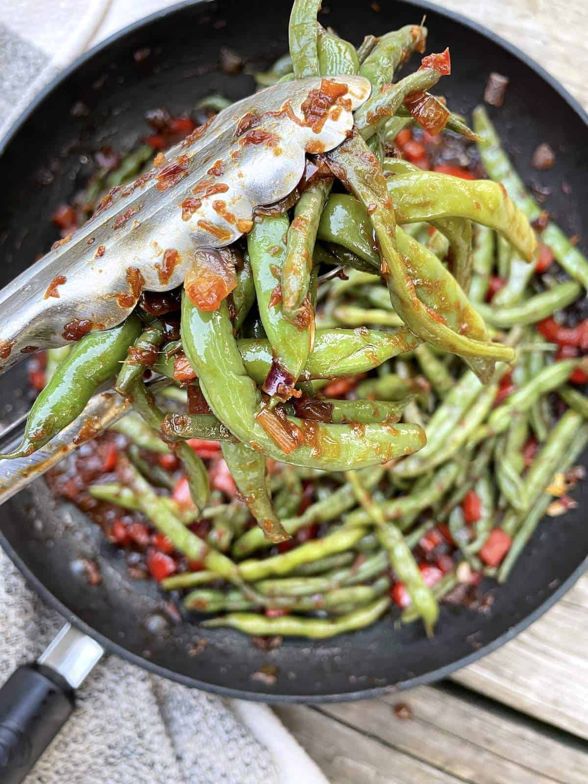 A pair of tongs holding sautéed green beans over a frying pan.